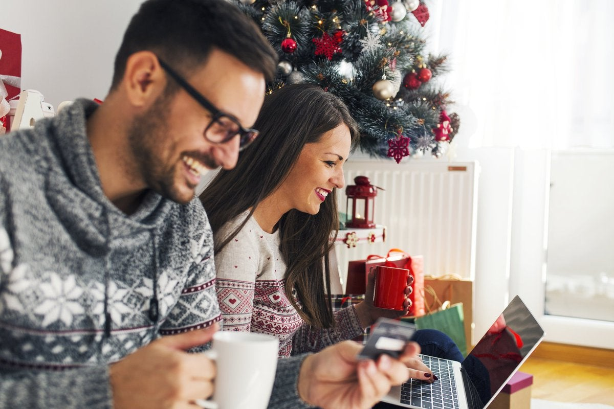 A smiling couple online shopping next to a Christmas tree.