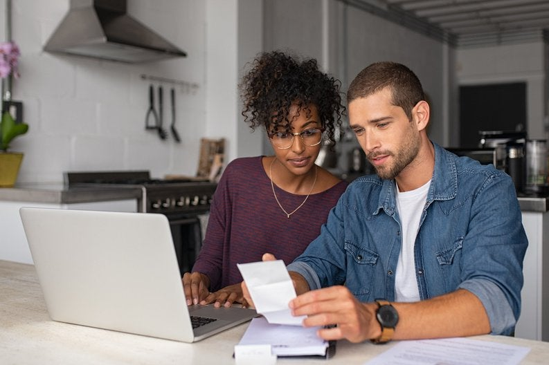 A young couple paying bills at their kitchen table.