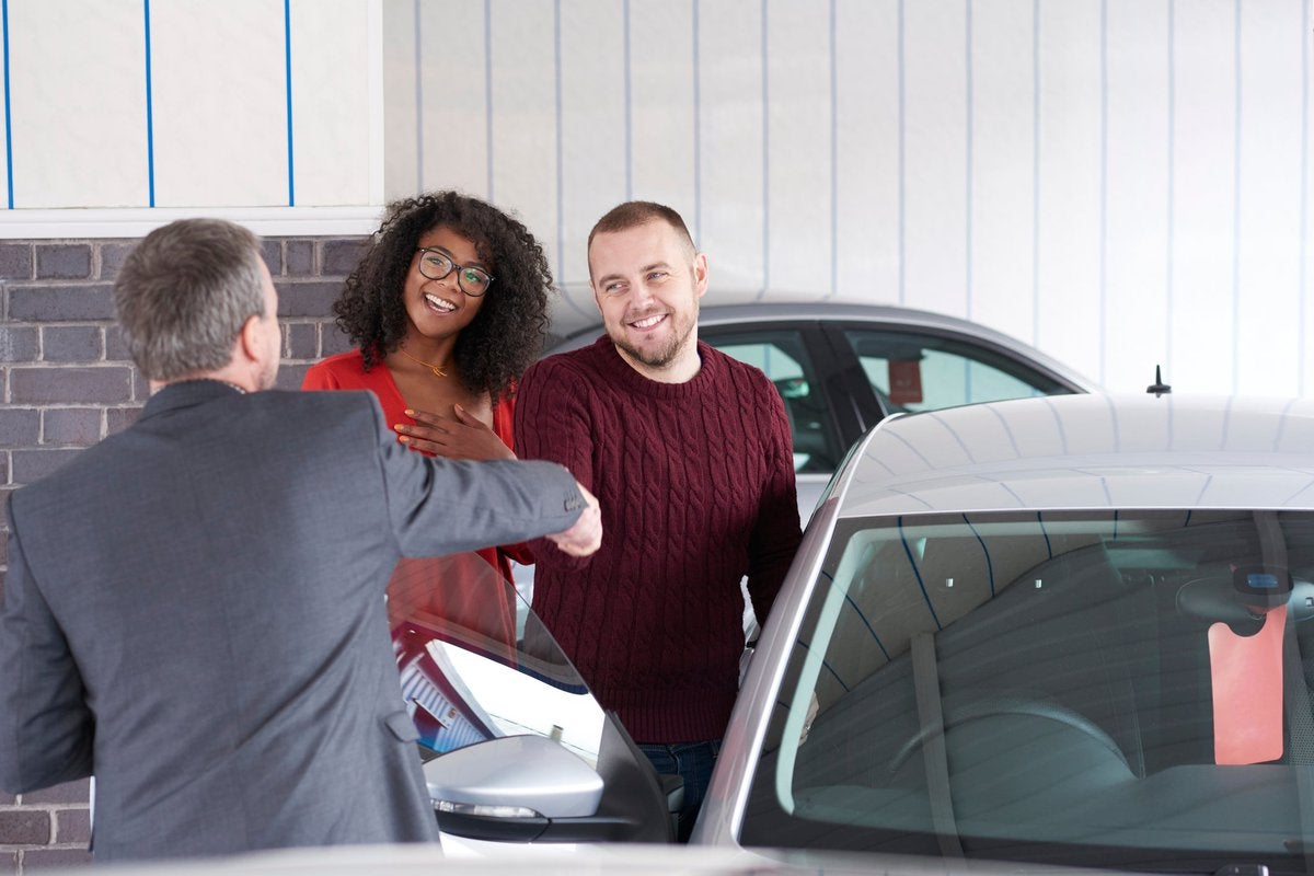 Couple shakes hand with a car salesman near a vehicle for sale.