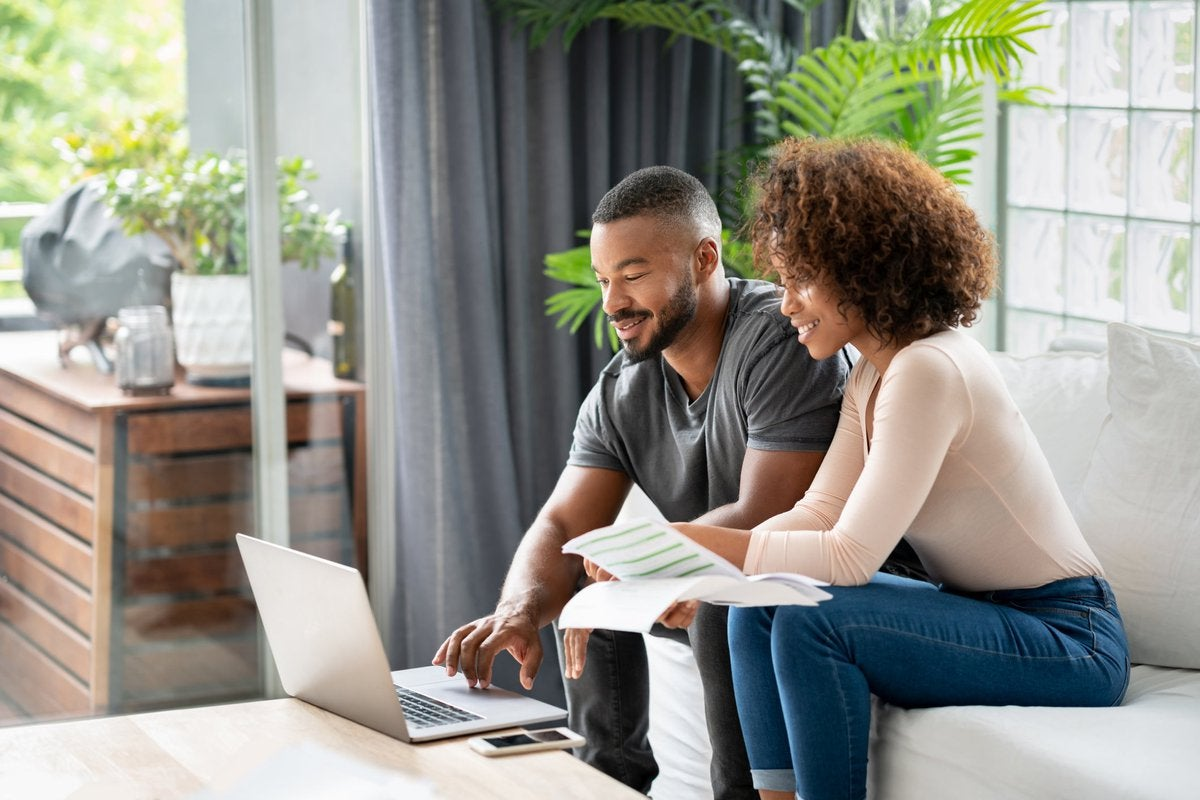 A couple sit in their living room and pay their credit card balances online.