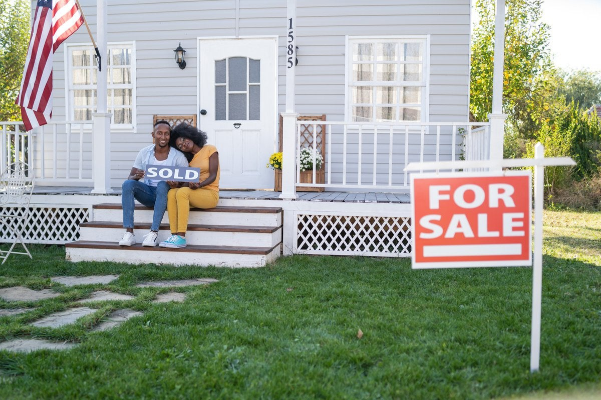 Couple sits on porch steps holding a house Sold sign.