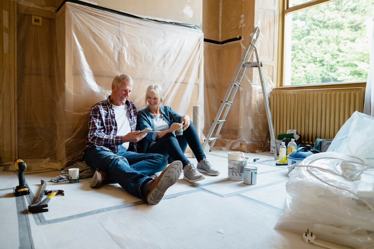 Couple sitting relaxing in a room that's undergoing renovation.