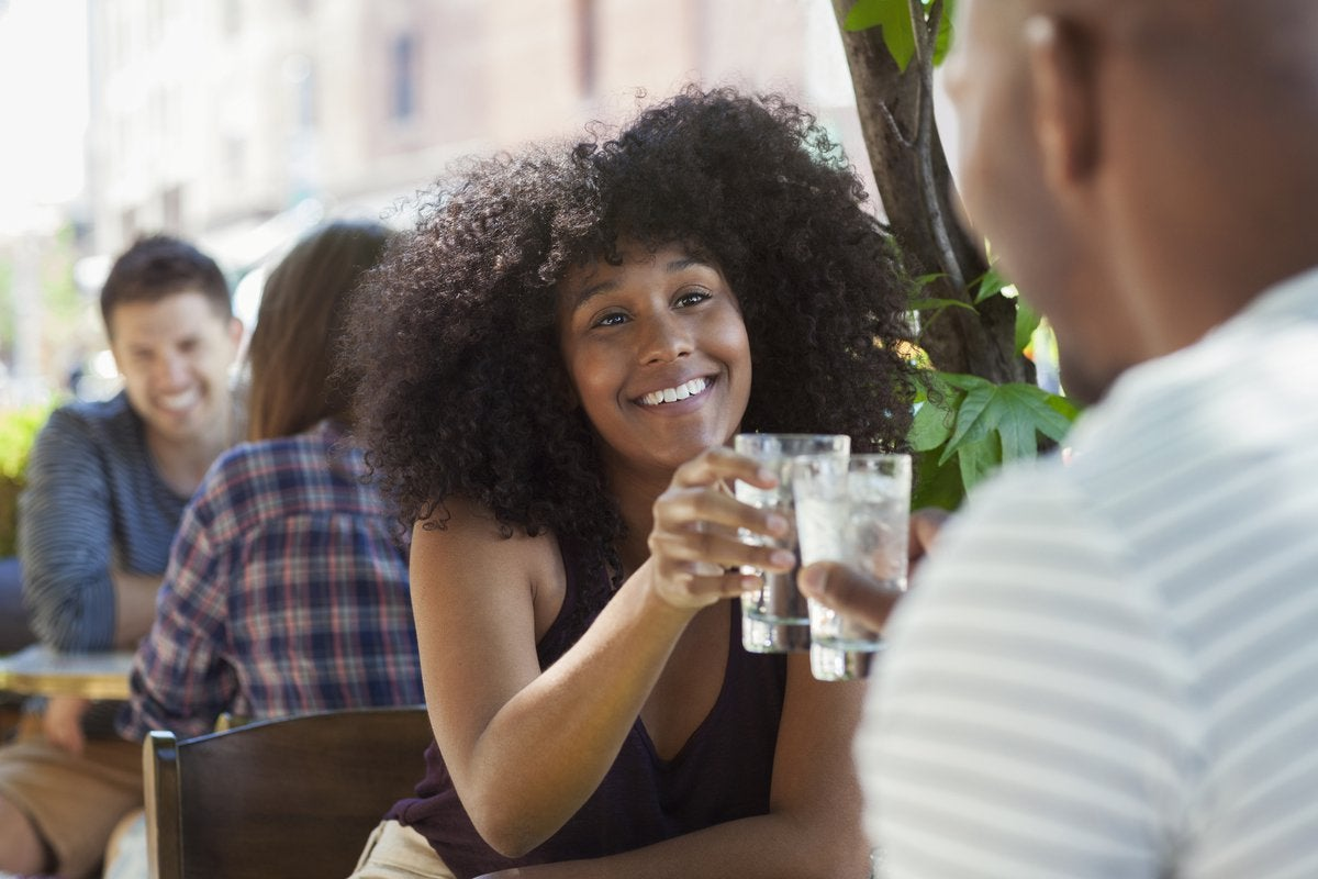 A couple are sitting together at a restaurant, smiling.