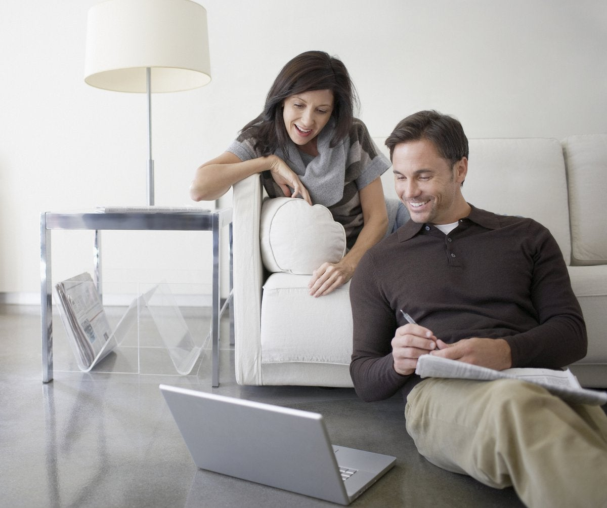 Couple looking at laptop screen together with smiles.