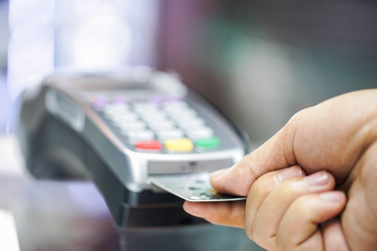 A person inserting a credit card into a credit card chip reader.
