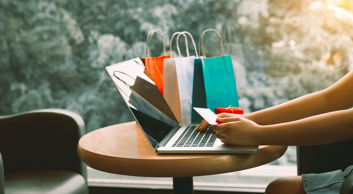 Someone using a credit card to shop on their laptop next to shopping bags on the table.