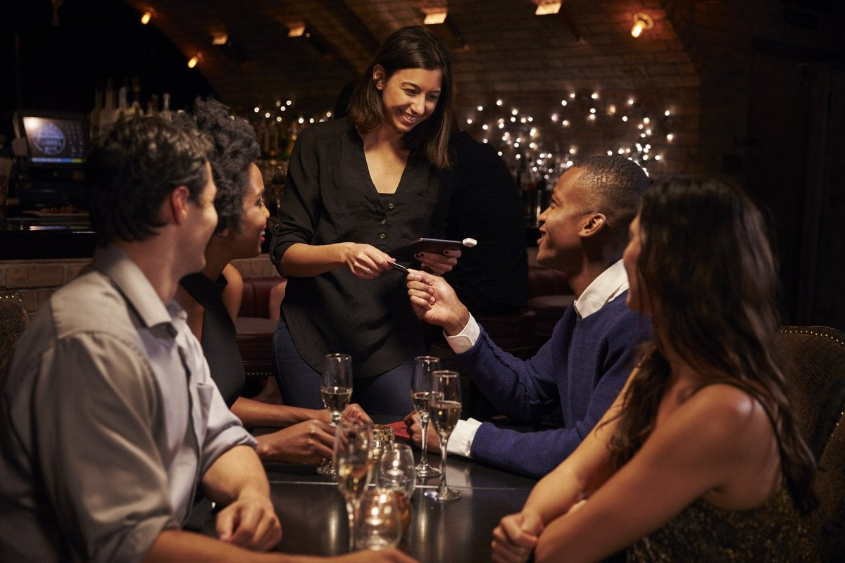 A waitress at a fancy restaurant accepting a credit card from a table of four diners.