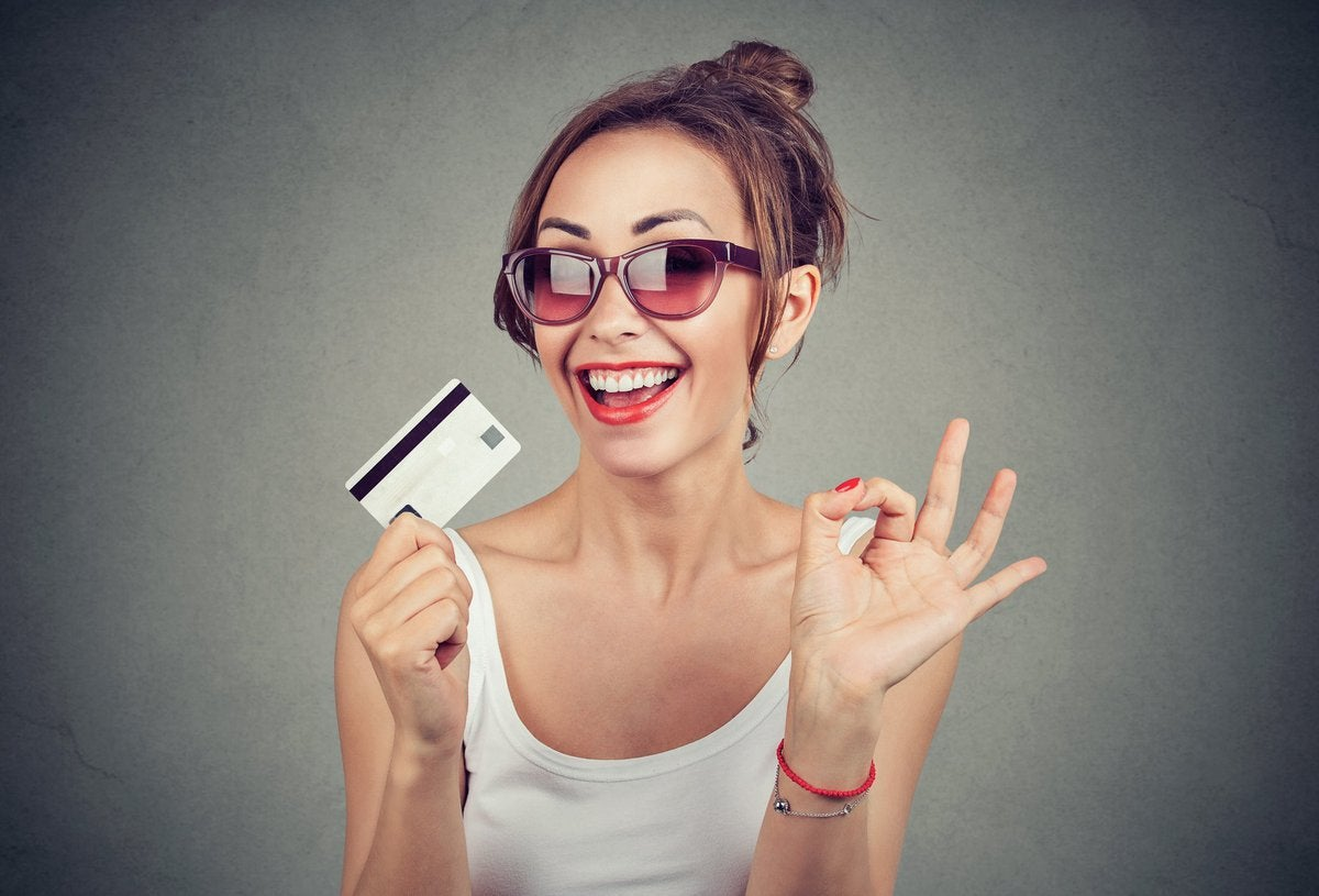 young woman in sunglasses holding a credit card and grinning