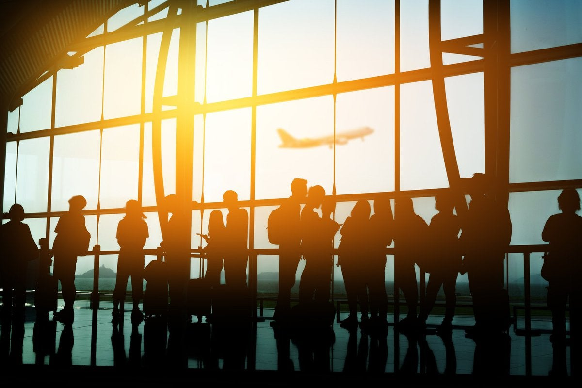 A crowd of people in front of a sunny airport window.