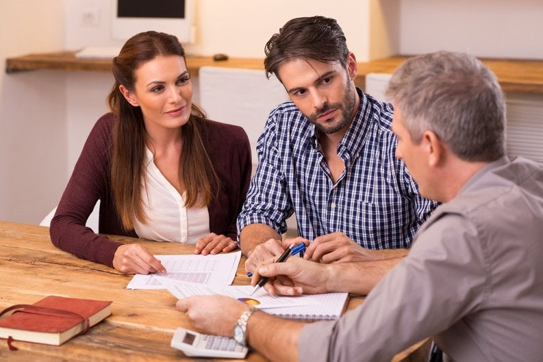 Three people sitting around a table with a calculator going over paperwork.