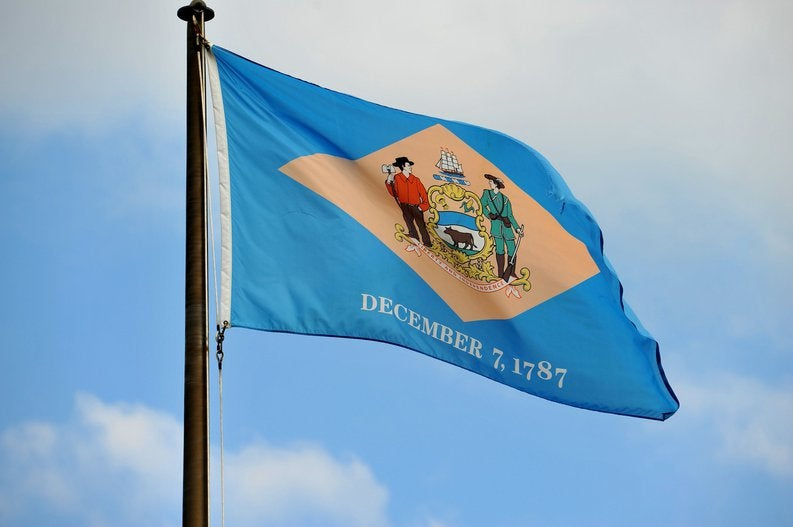 The Delaware state flag flying in front of a blue sky and white clouds.