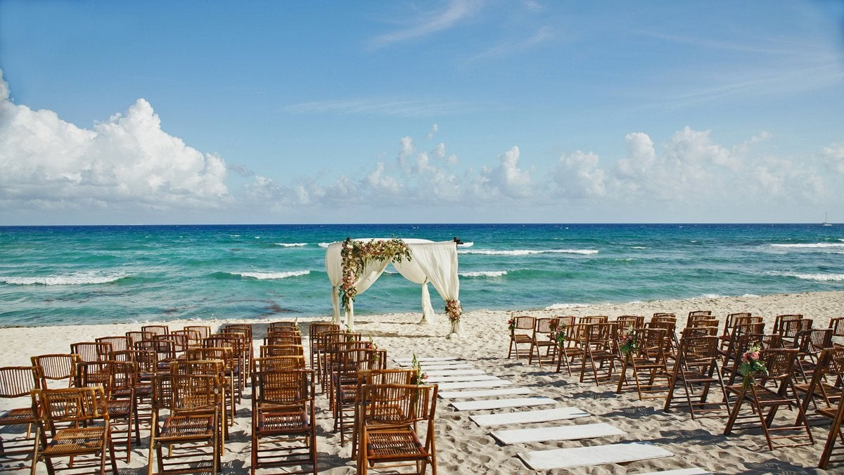 Chairs set up on the beach for a wedding ceremony.