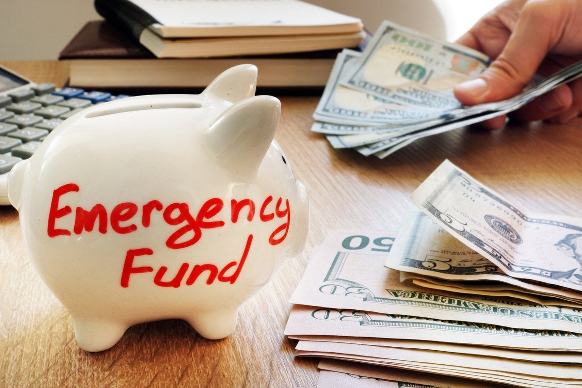 A white piggy bank that says emergency fund next to a stack of U.S. currency.