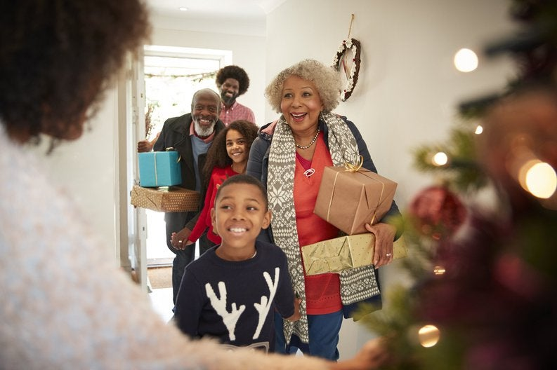 A happy family walking into a home with wrapped gifts.
