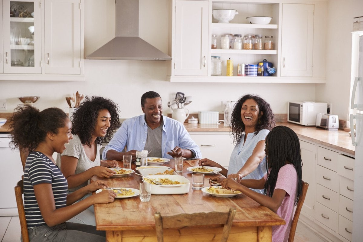 A smiling family eating breakfast together at the kitchen table.