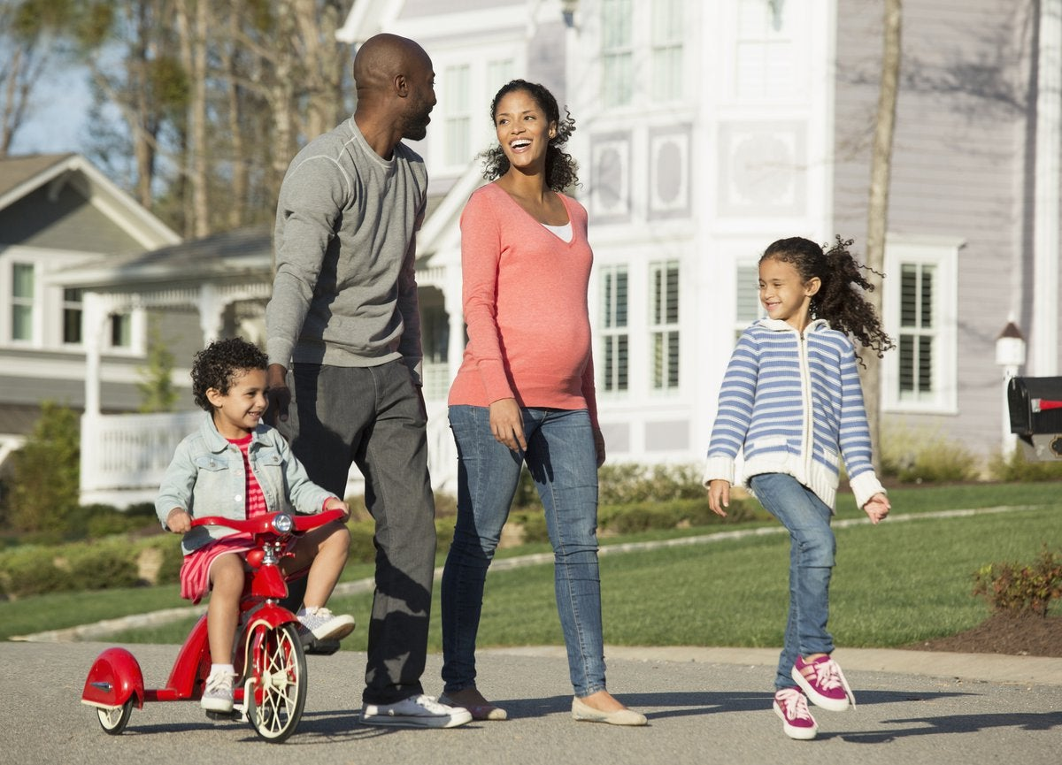 Couple walking through suburban neighborhood with youngest child riding a tricycle.