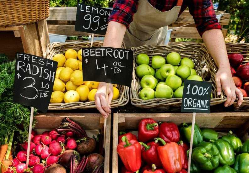 Person putting price signs on vegetables at the farmers market