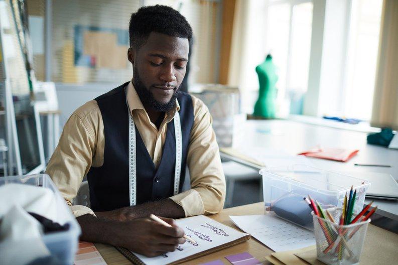 A man in a fashion design studio sketching ideas.