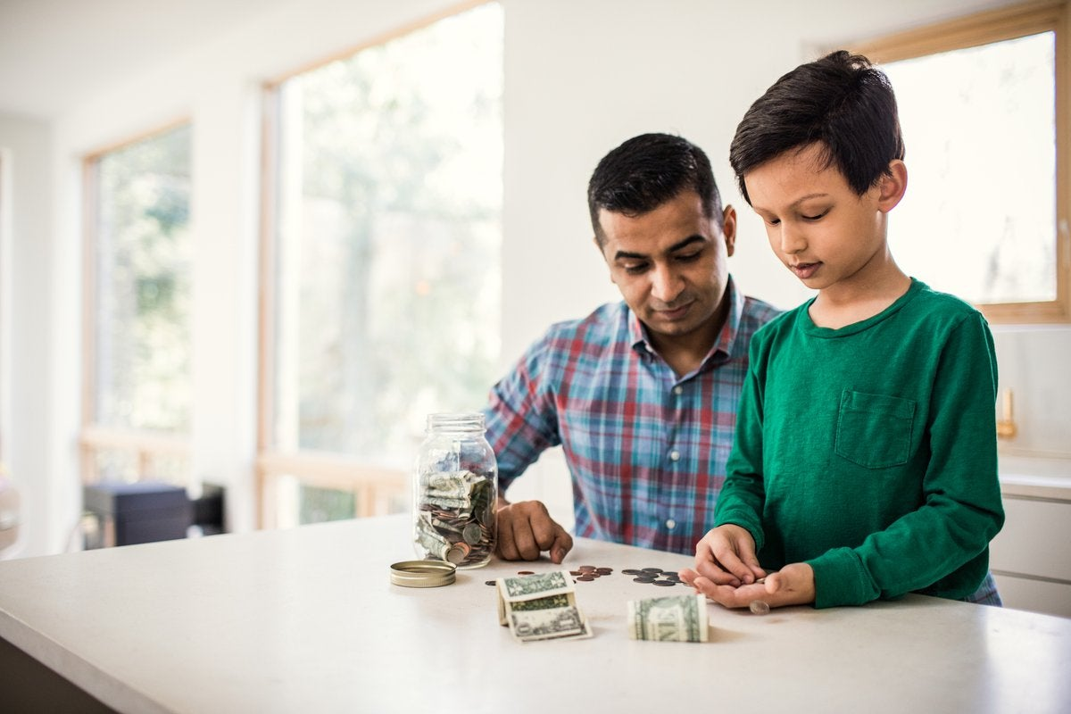 Father and son counting money at home.