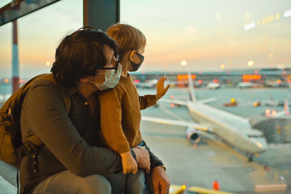 Father and son in masks looking out airport window.