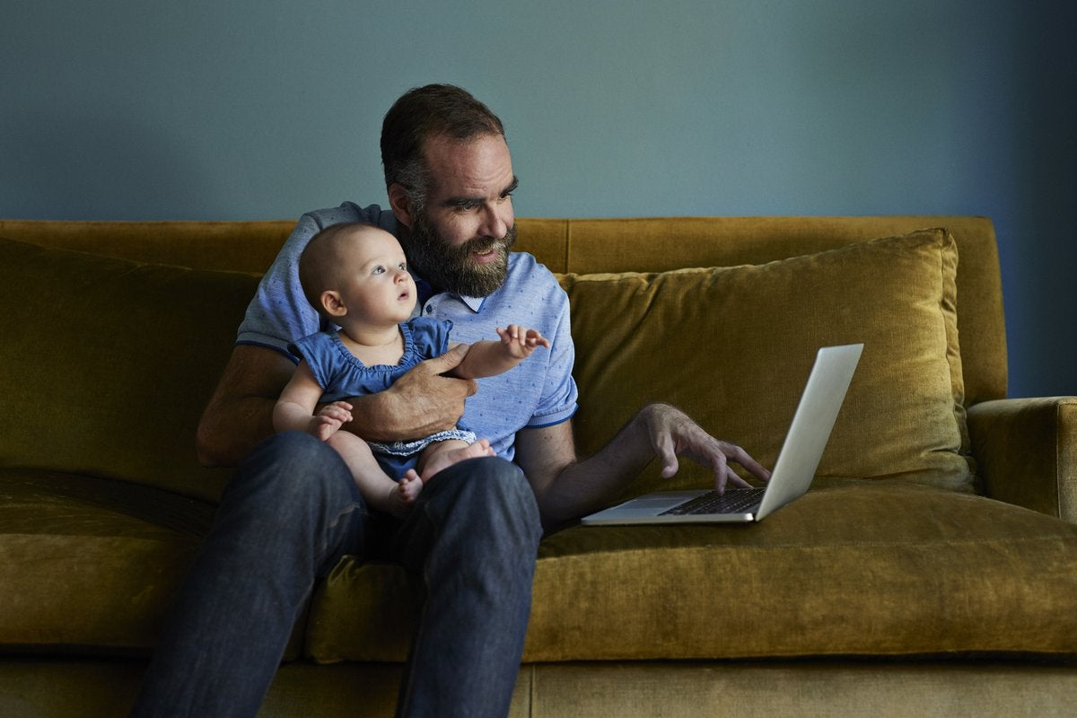 A father sits on a sofa with his baby while working on his laptop.