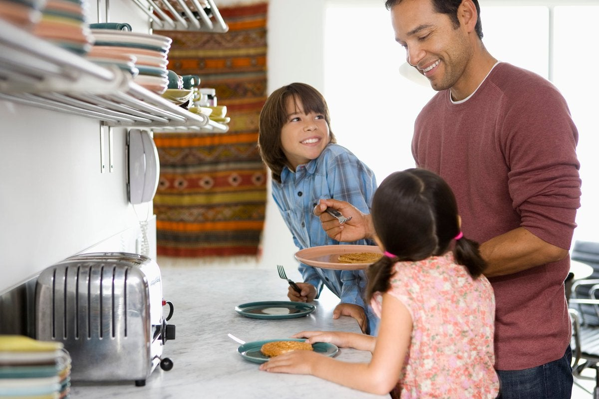 Father in kitchen with kids making breakfast