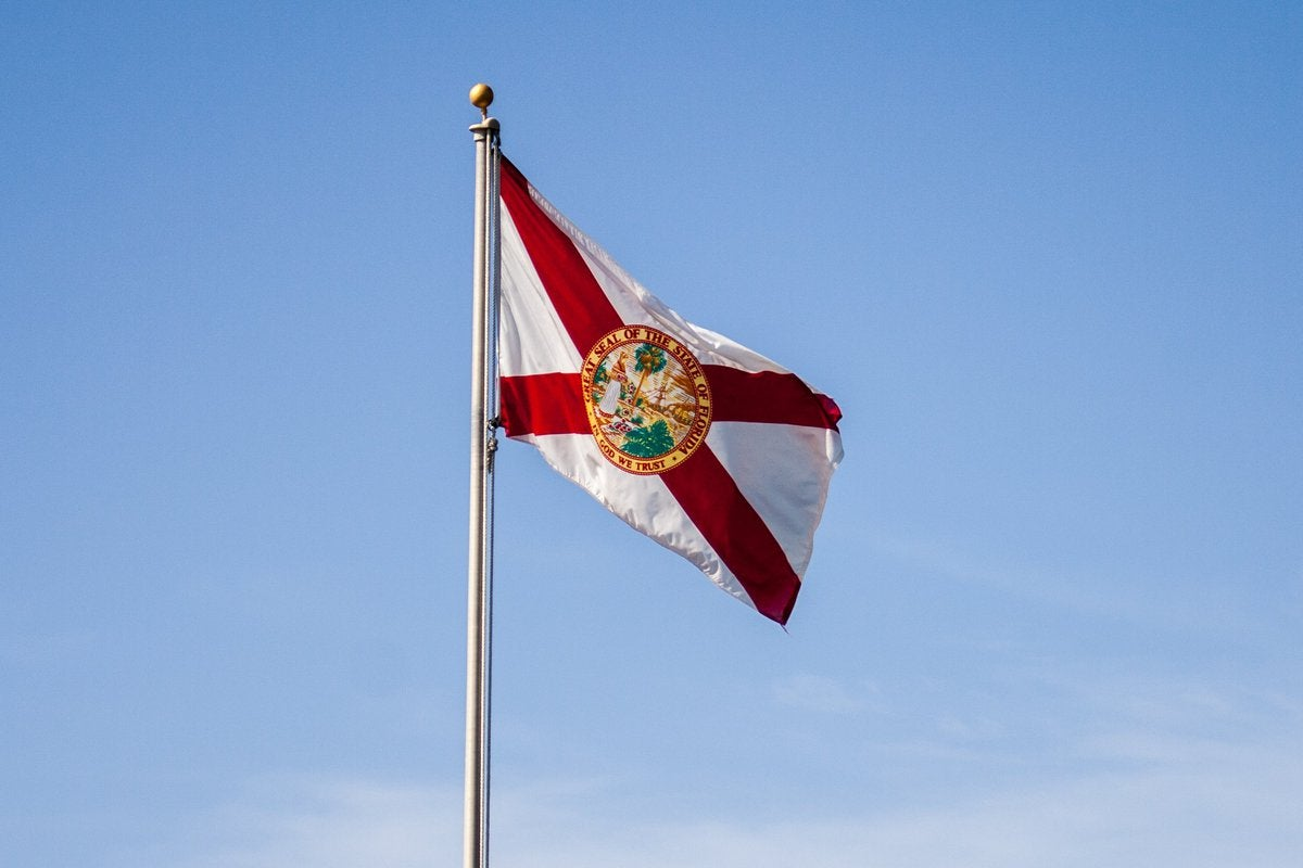 The Florida state flag flying in front of a blue sky.