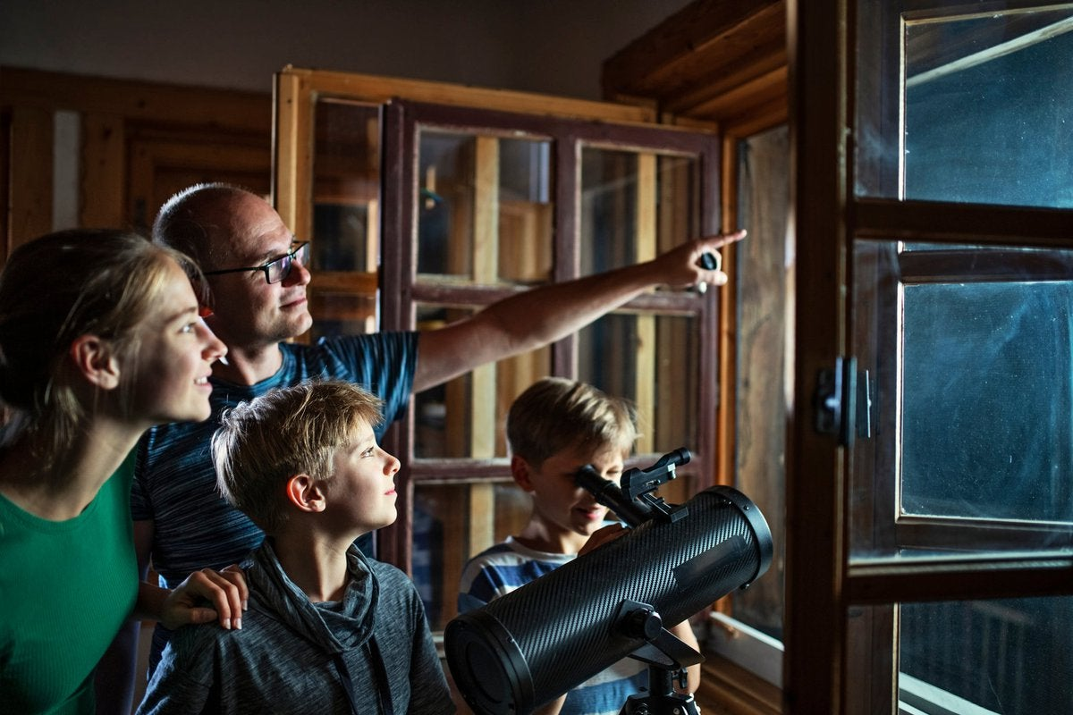 Family looking at the night sky through a telescope.