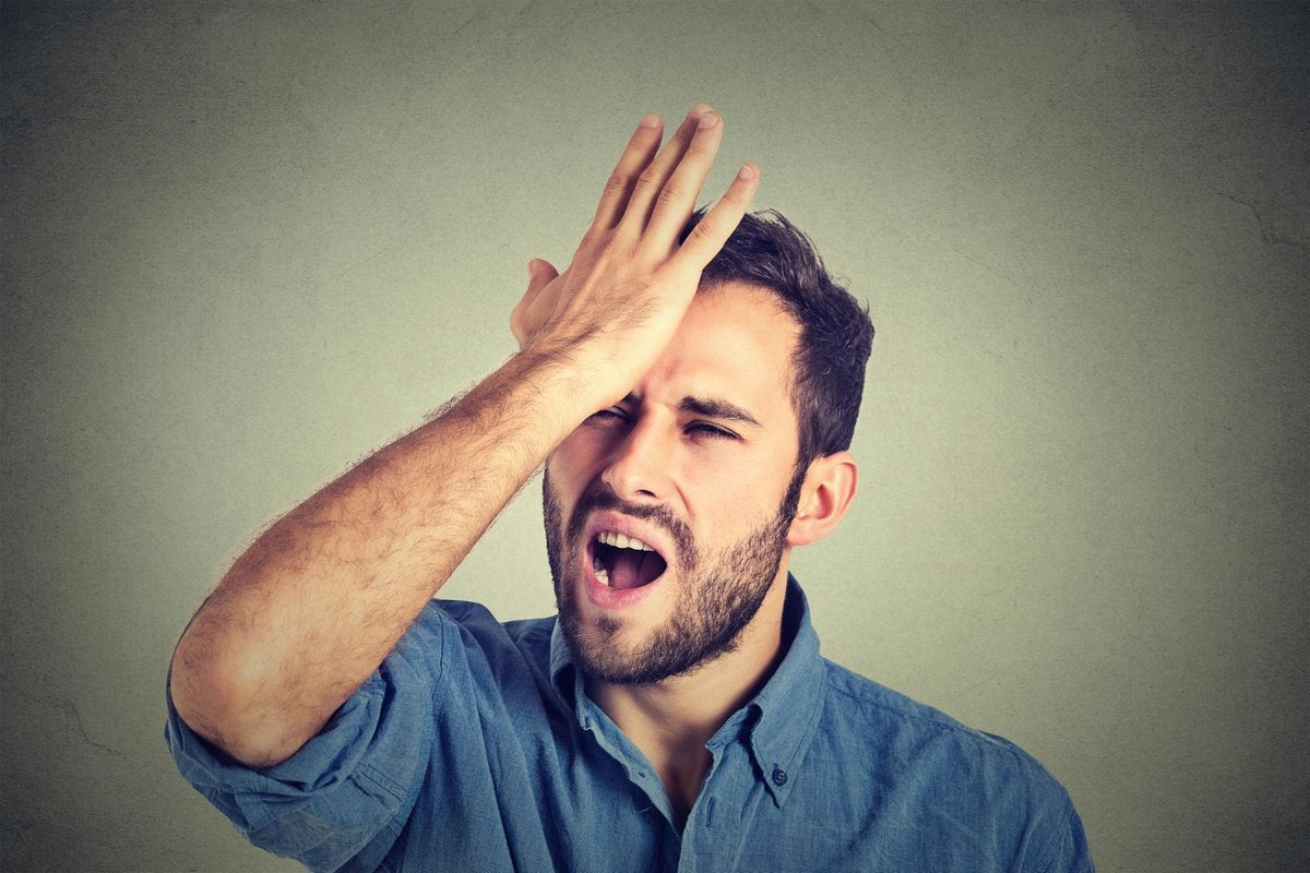 Upset man smacking his forehead with his hand