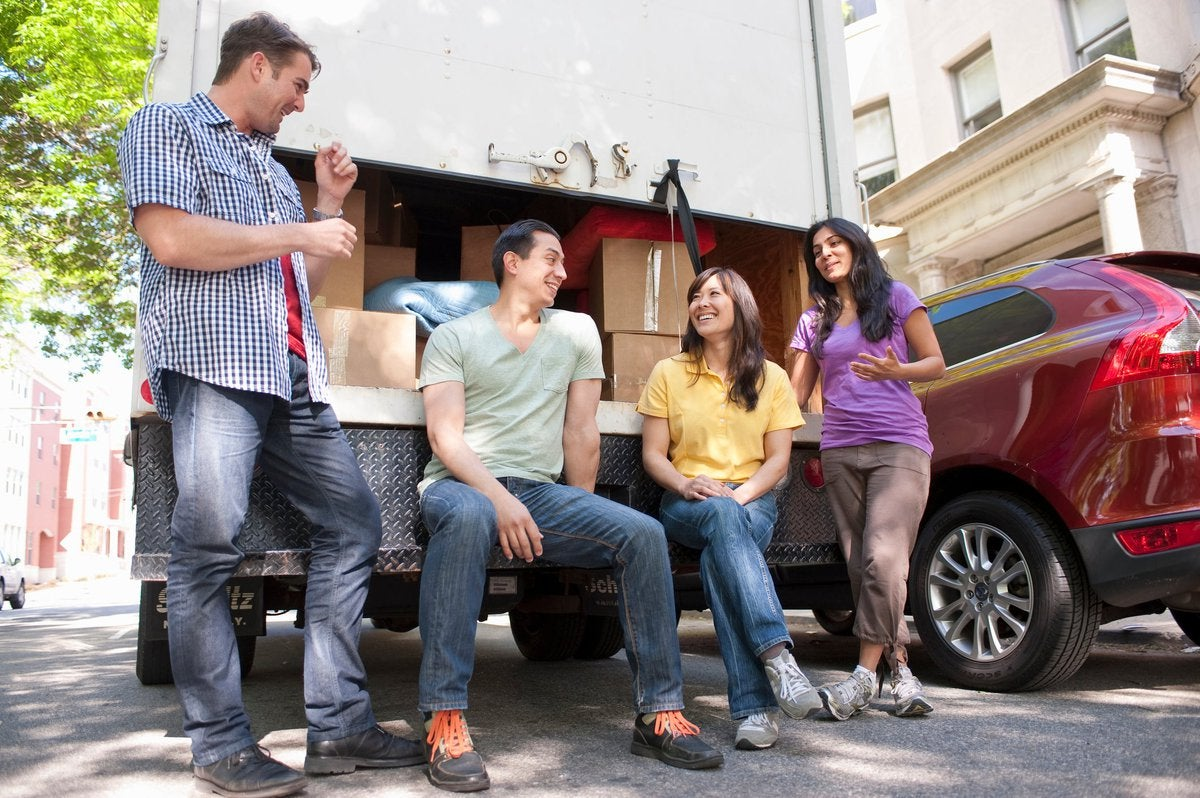 Four adults hanging out by loaded moving truck and car.