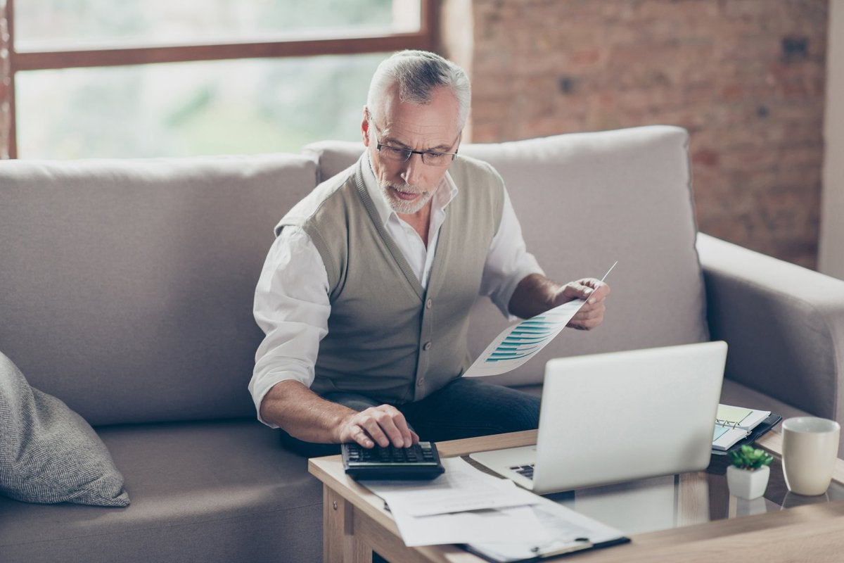 Older man using calculator and laptop.