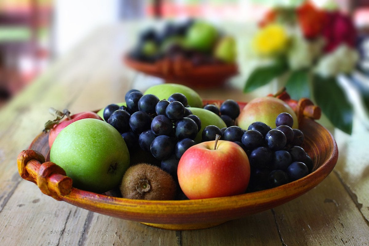 A wooden bowl full of a fruit on a counter.