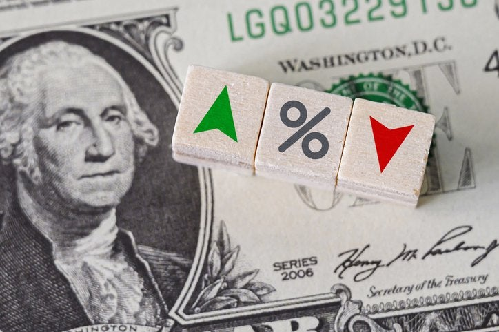 Blocks with up and down and percent signs on top of a dollar bill with George Washington showing.
