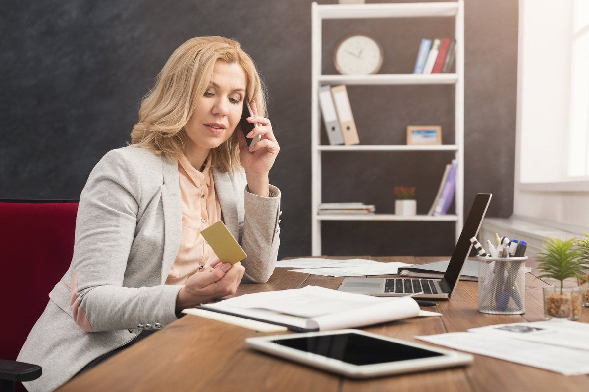 Woman at desk talking on cell phone while holding credit card.