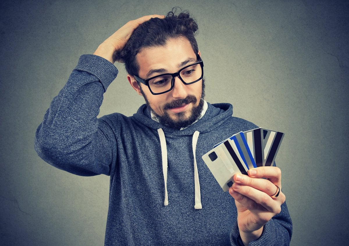 Bespectacled young man looking at the numerous credit cards in his hand with confused disbelief.