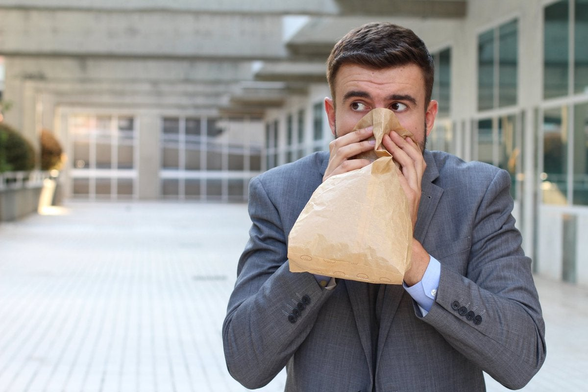 Young man in suit hyperventilating into paper bag.