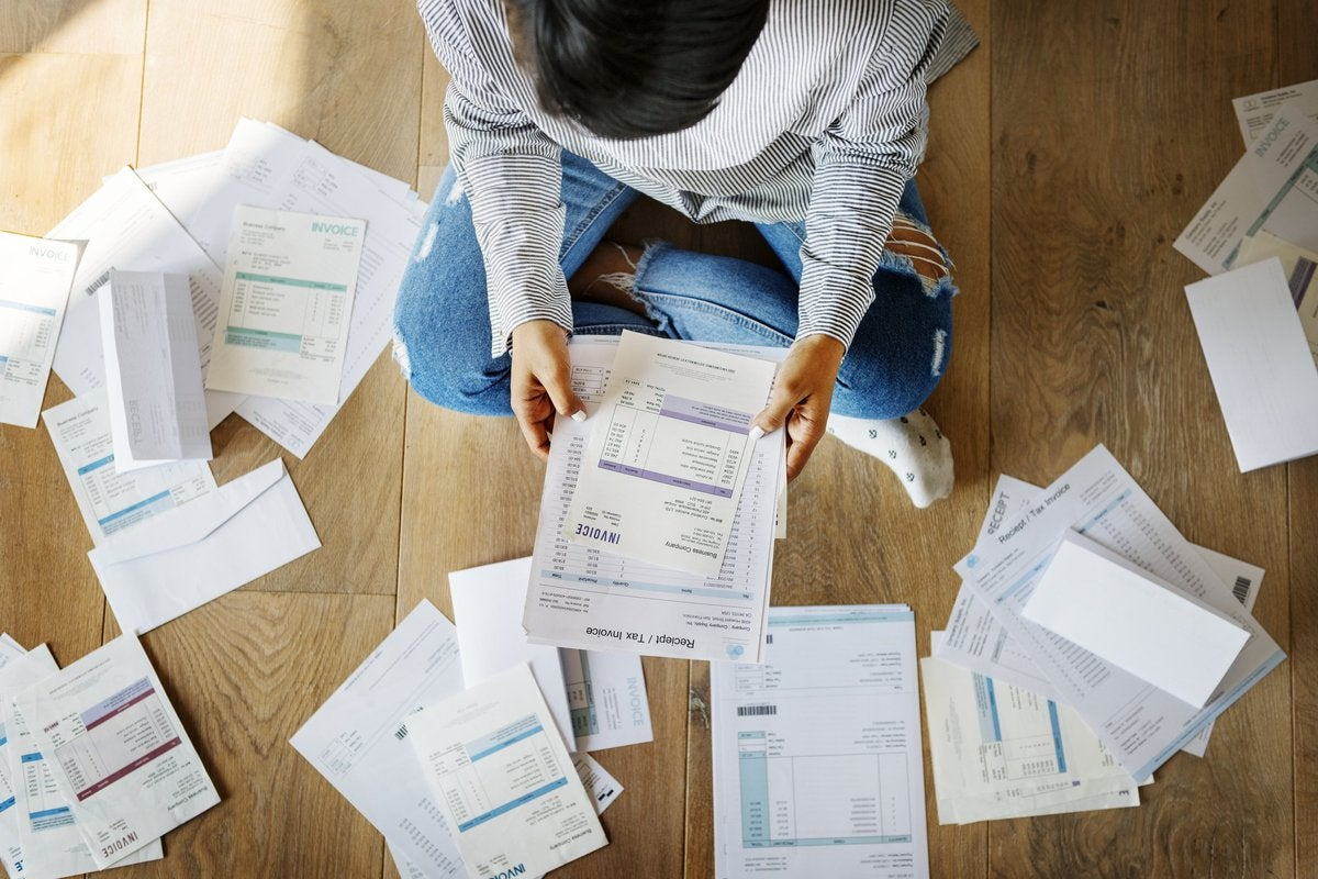 Man sitting on floor surrounded by bills.