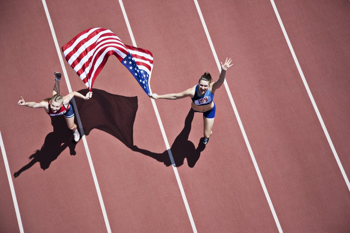 Bird's eye view of two female track runners holding an American flag and waving.