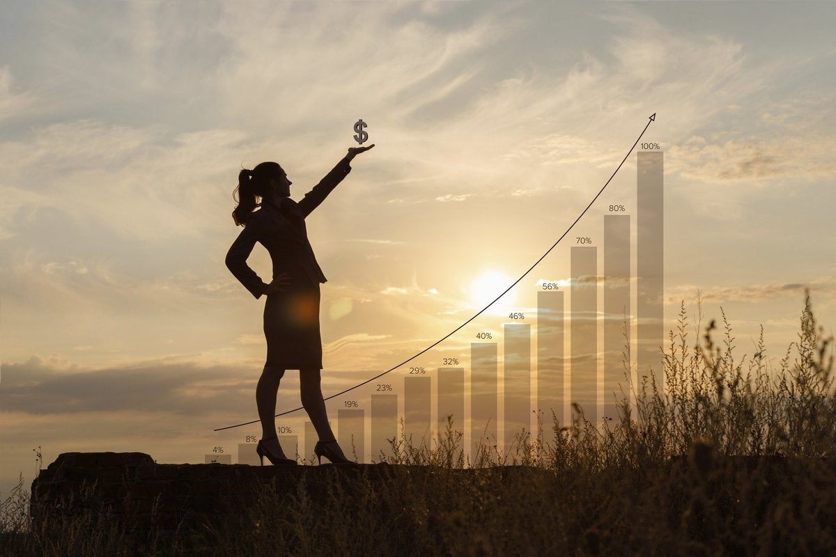 Silhouette of a woman standing in a field at sunset holding a dollar sign up to the sky.