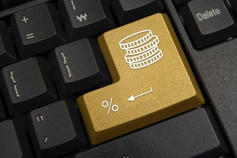 A computer keyboard featuring a golden return key marked with a stack of coins and a percentage sign.