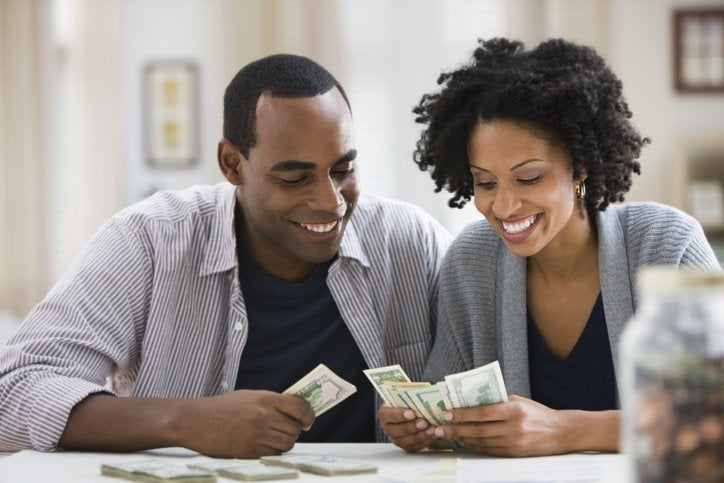 An African American couple counts the bills they've earned. A jar full of coins is in the foreground.
