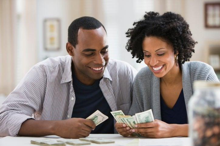 Smiling couple counting money in their hands.