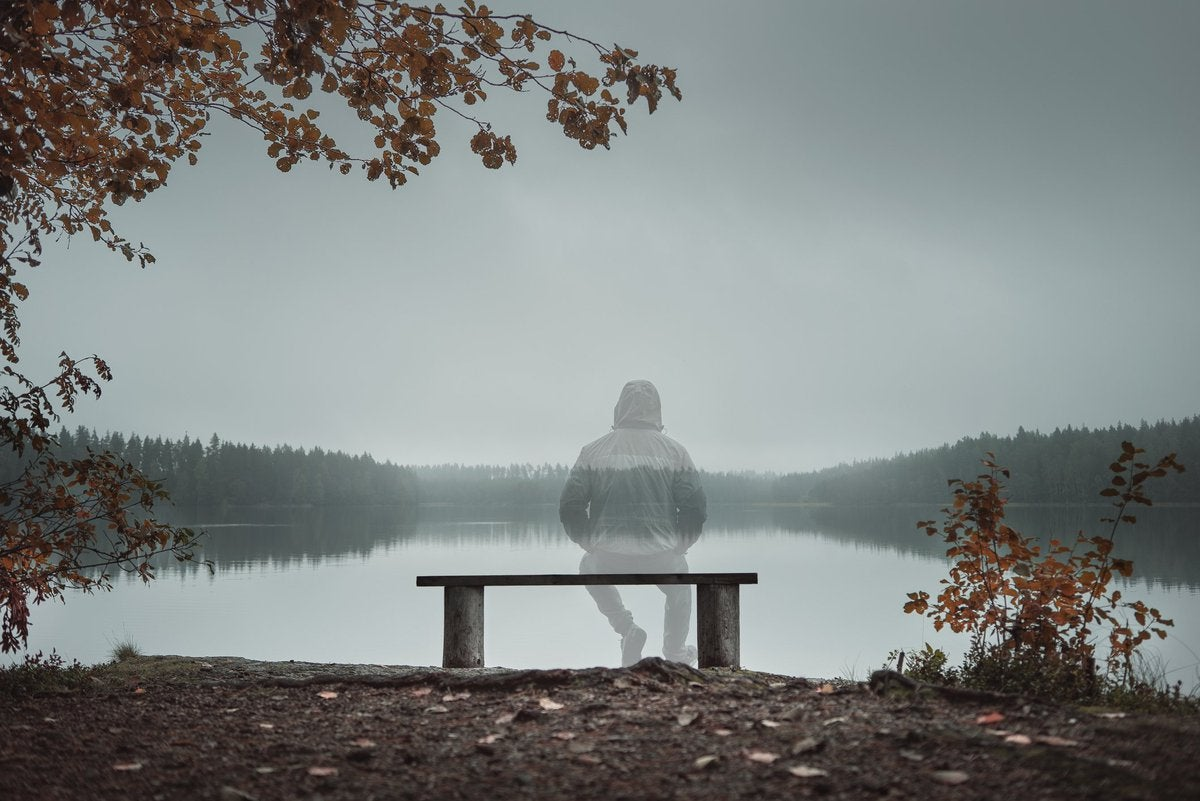 A man sitting on a bench looking out at a wintry lake and fading into physical transparency.