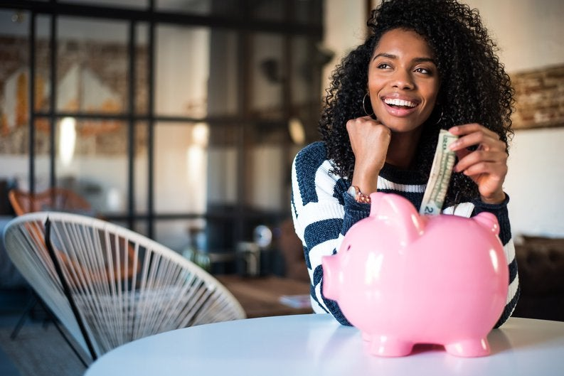 Young woman looking off and smiling while putting a 20-dollar bill in a piggy bank.