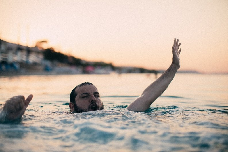 Bearded guy flailing around in the ocean.