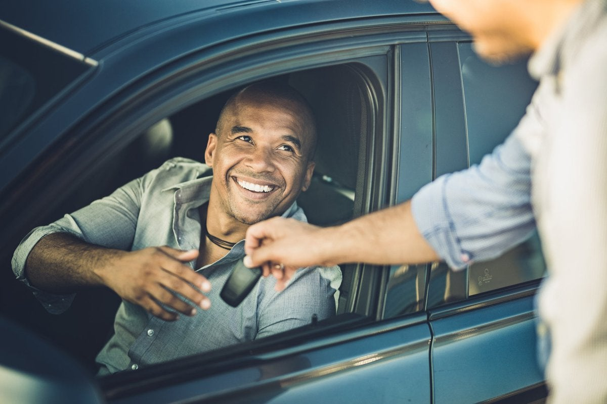 A smiling person in a car receives car keys.