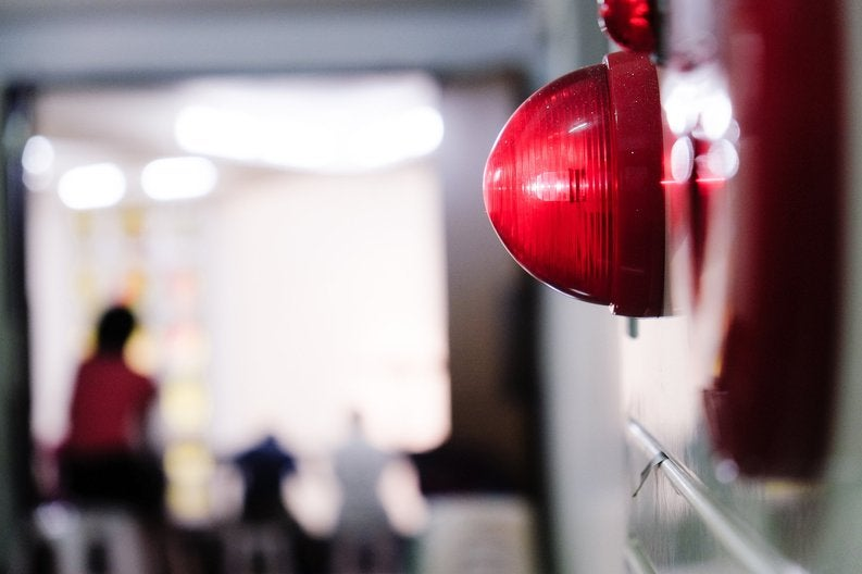 A lit-up red wall alarm.