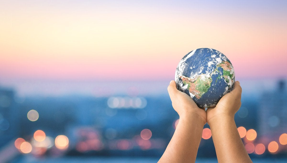 A pair of hands raising forth a small-scale model of planet Earth.