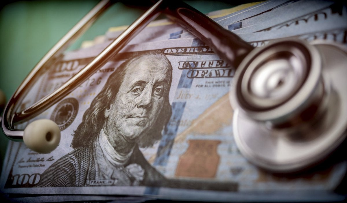 A stethoscope listening in to what's happening inside a stack of 100 dollar bills.