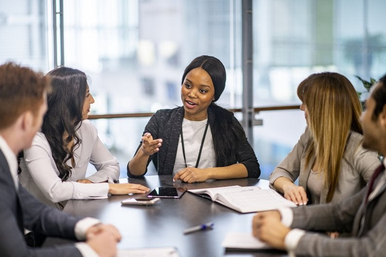Young woman sitting at the head of a conference table leading a discussion with several co-workers.